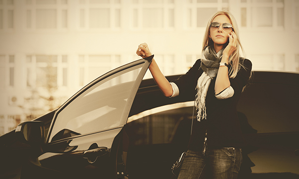 Fashion business woman talking on mobile phone beside a her car Stylish female model in black blazer and sunglasses outdoor
